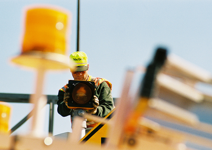 Man wearing MnDOT safety gear holds up a signal lighting component