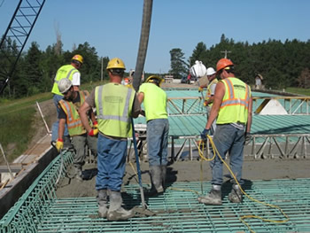 Construction workers pour a new deck on the 15th Street bridge along the Bemidji 2/71 bypass