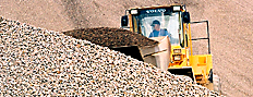 Pay loader scooping from an aggregate pile