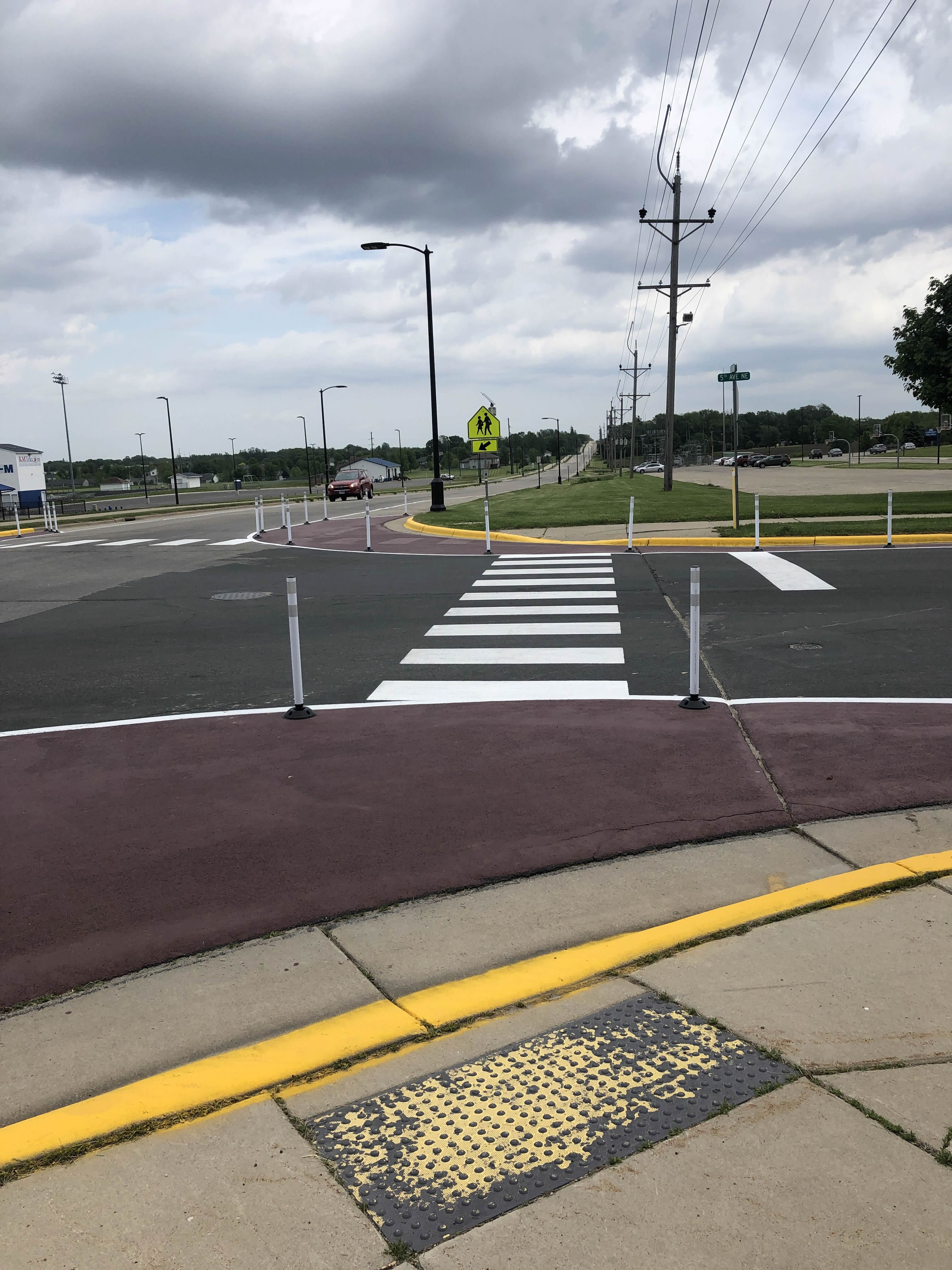 A finished demonstration project, including painted curb extensions, white flexible posts, and a freshly painted high-visibility white crosswalk.