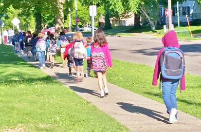 photo of students walking to school on sidewalk