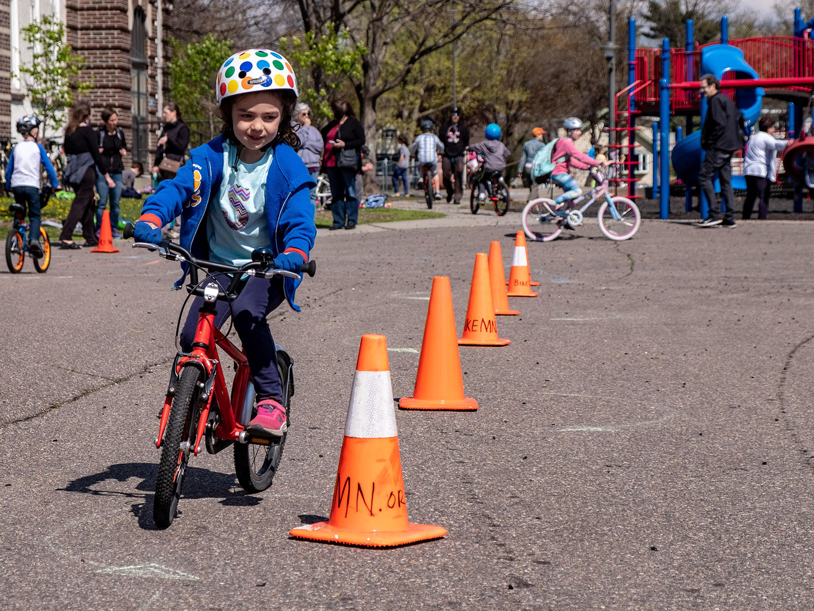 A child riding a bike around orange traffic cones