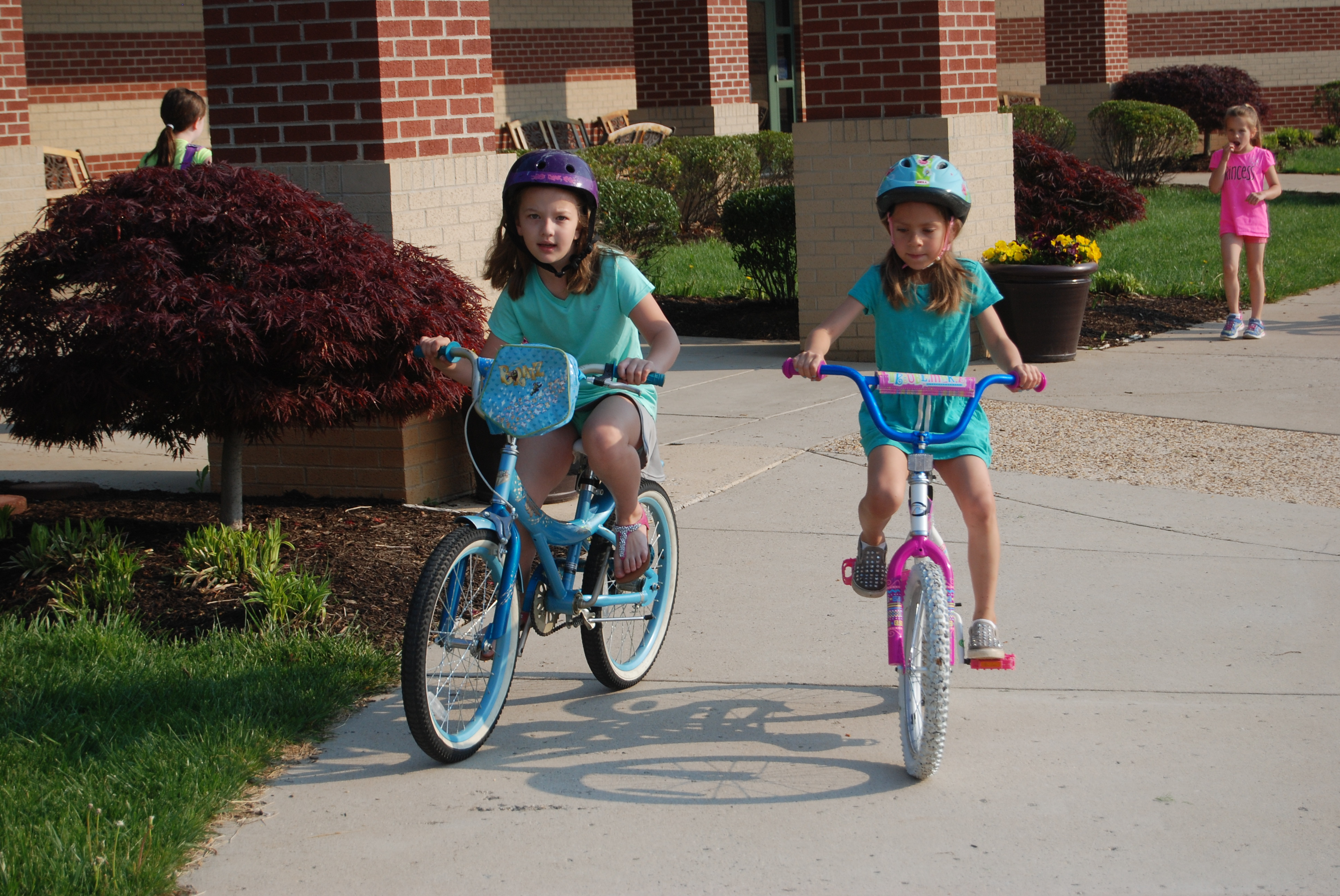 Two young girls riding bicycles on a school sidewalk