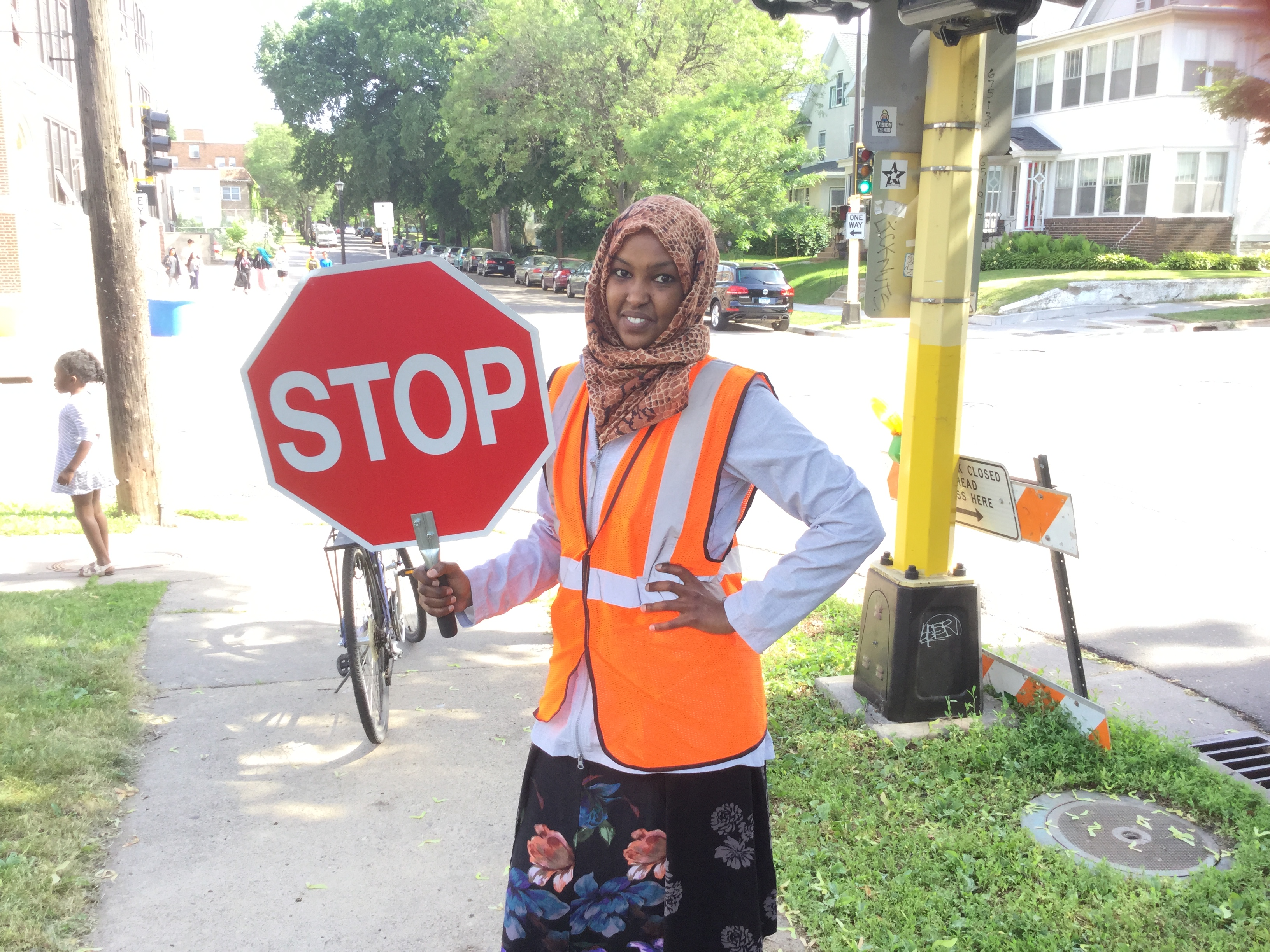 A person wearing a hijab smiling and holding a stop sign