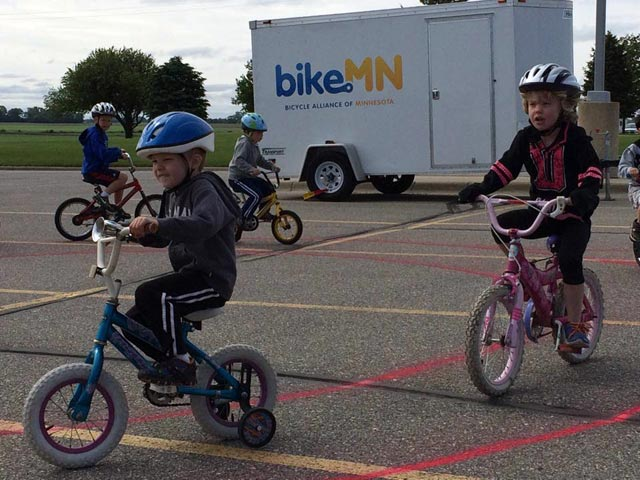 Small children riding bicylces with training wheels