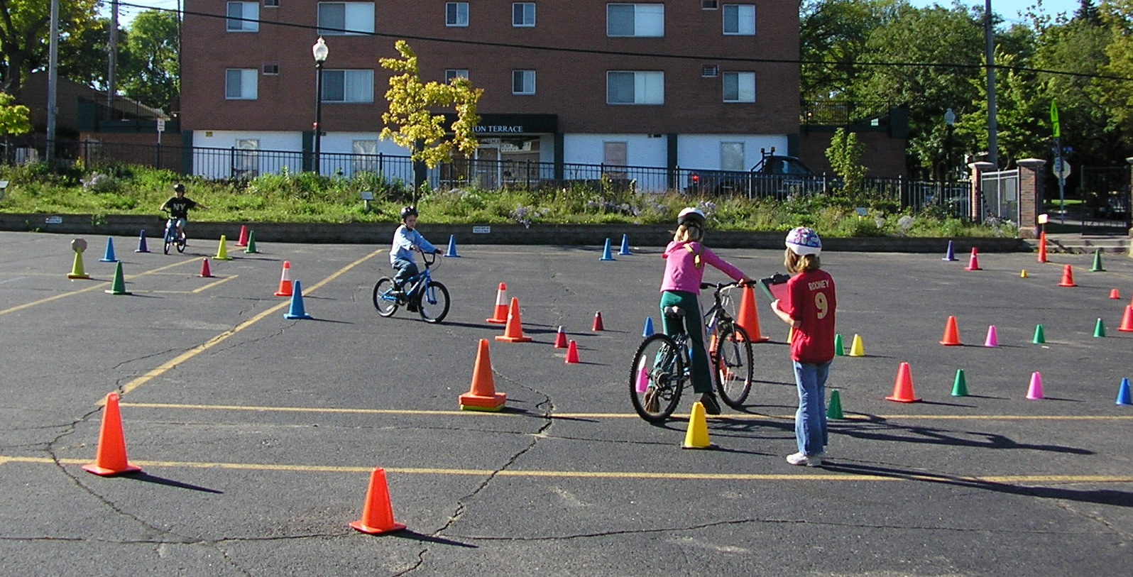 Children riding bicycles through a course of traffic cones