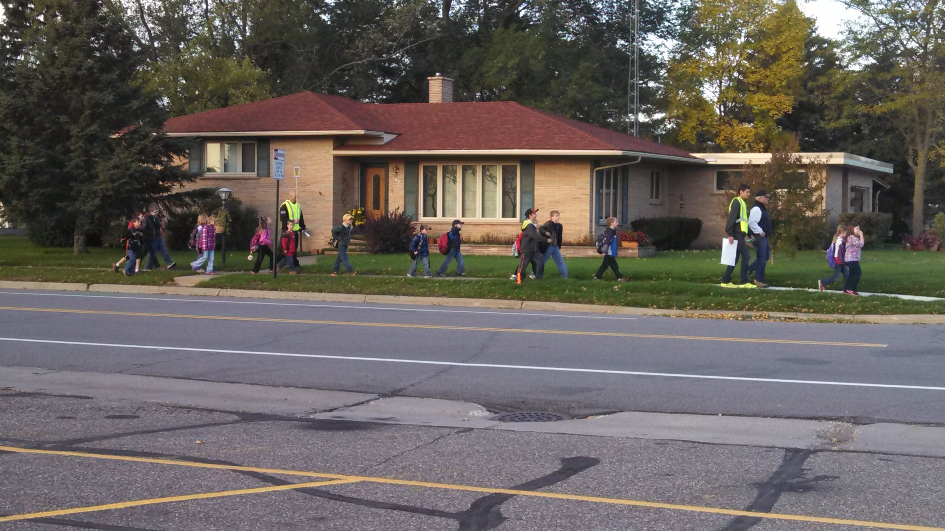 A group of children with adult crossing guards walking along a sidewalk