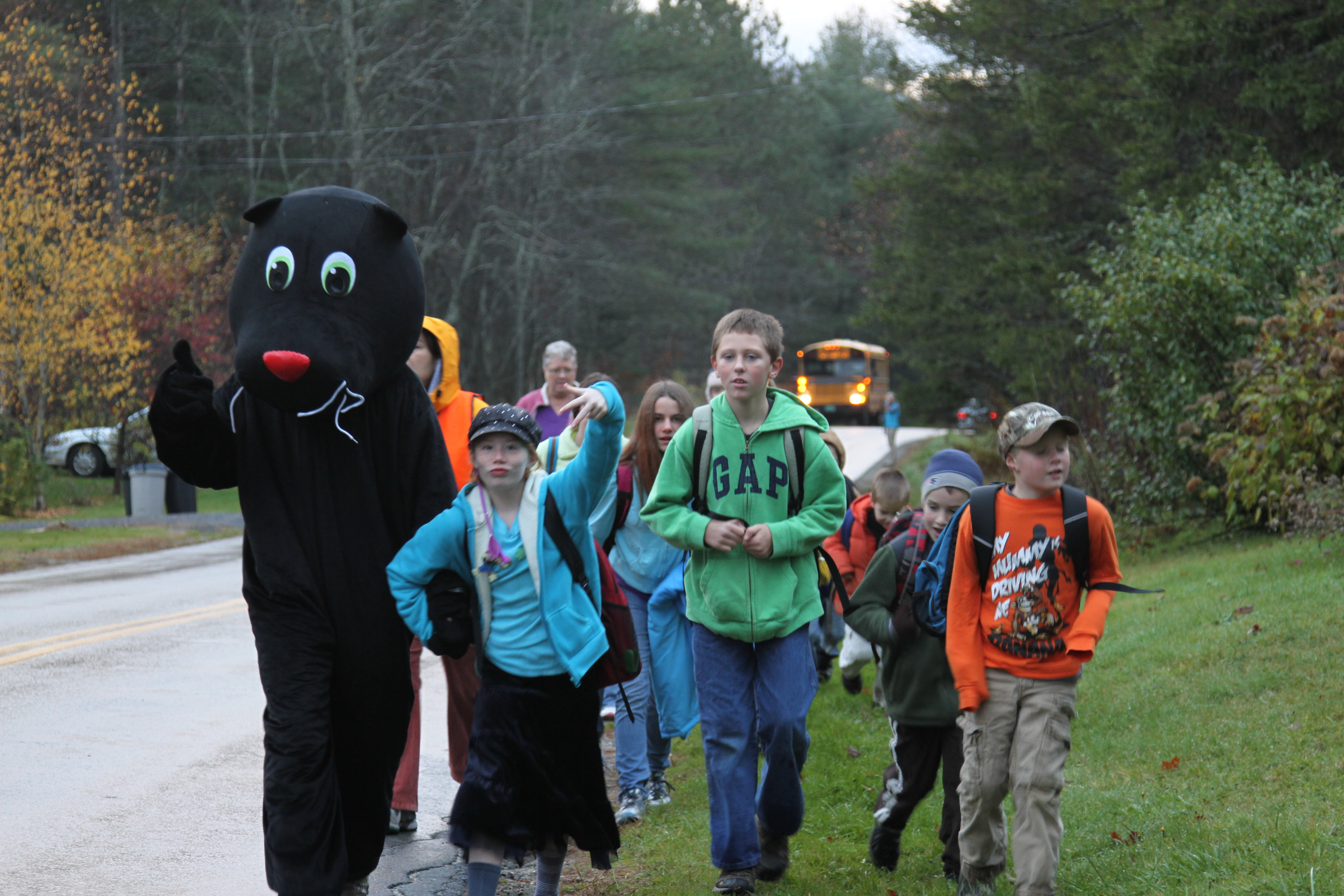 Children walking alongside a roadway with a school mascot