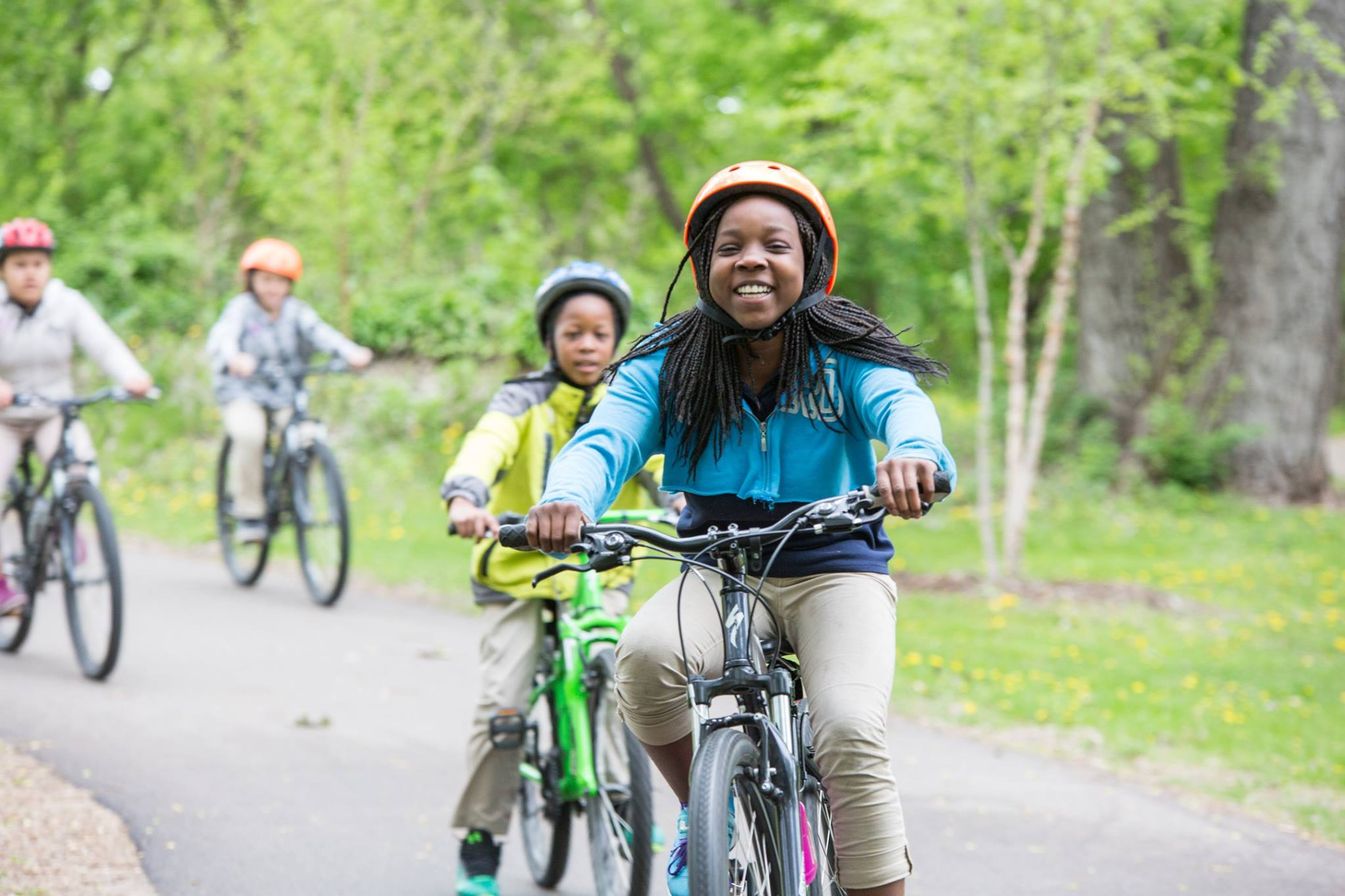 A child wearing a helmet smiles and pedals a bike. There are other children riding bikes in the background.