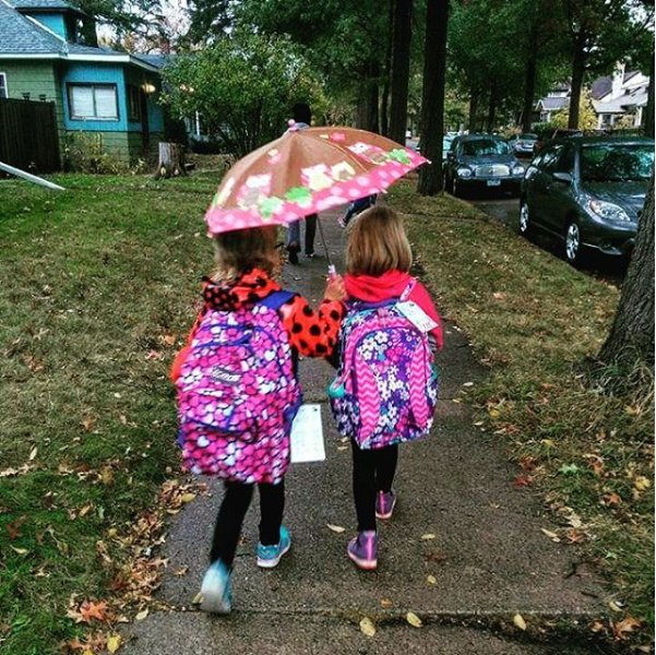 Two girls walking to school in rain