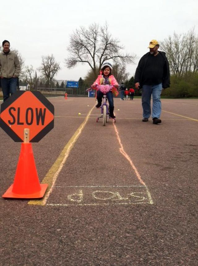 Photo of a child learning bike riding and safety skills.