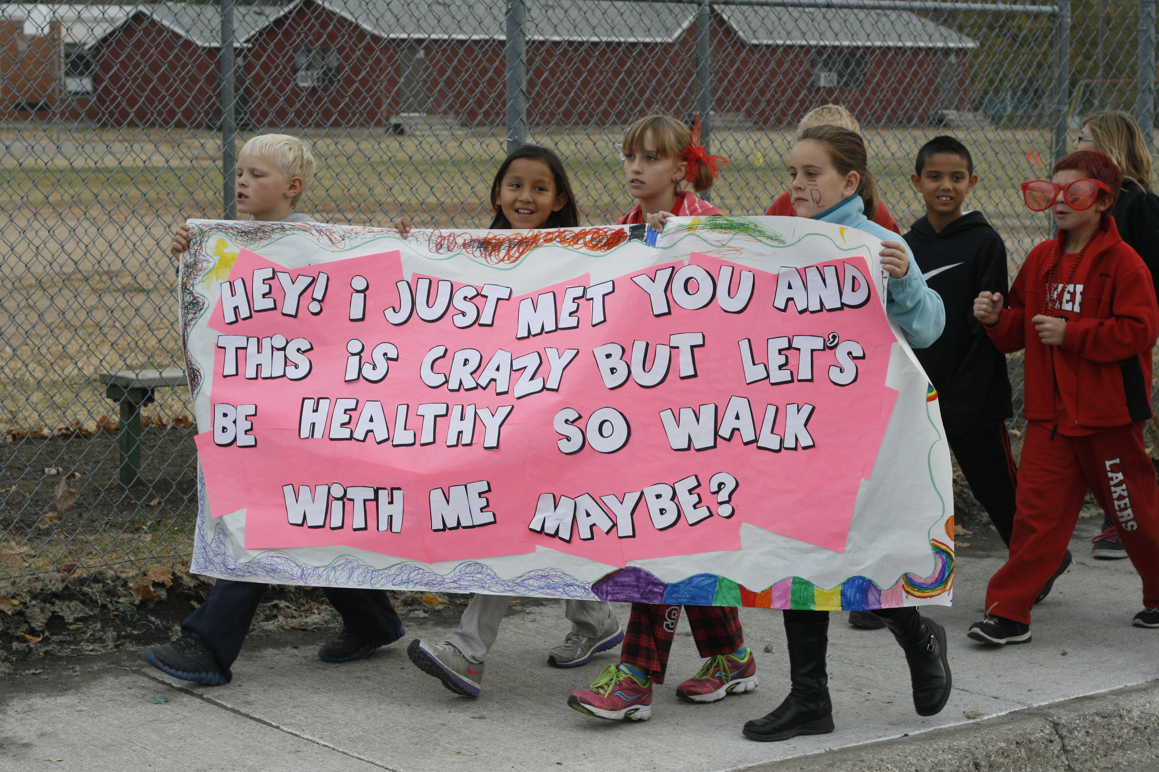"Children walking with a sign that says, ""Hey! I just met you and this is crazy but let's be healthy so walk with me maybe?"