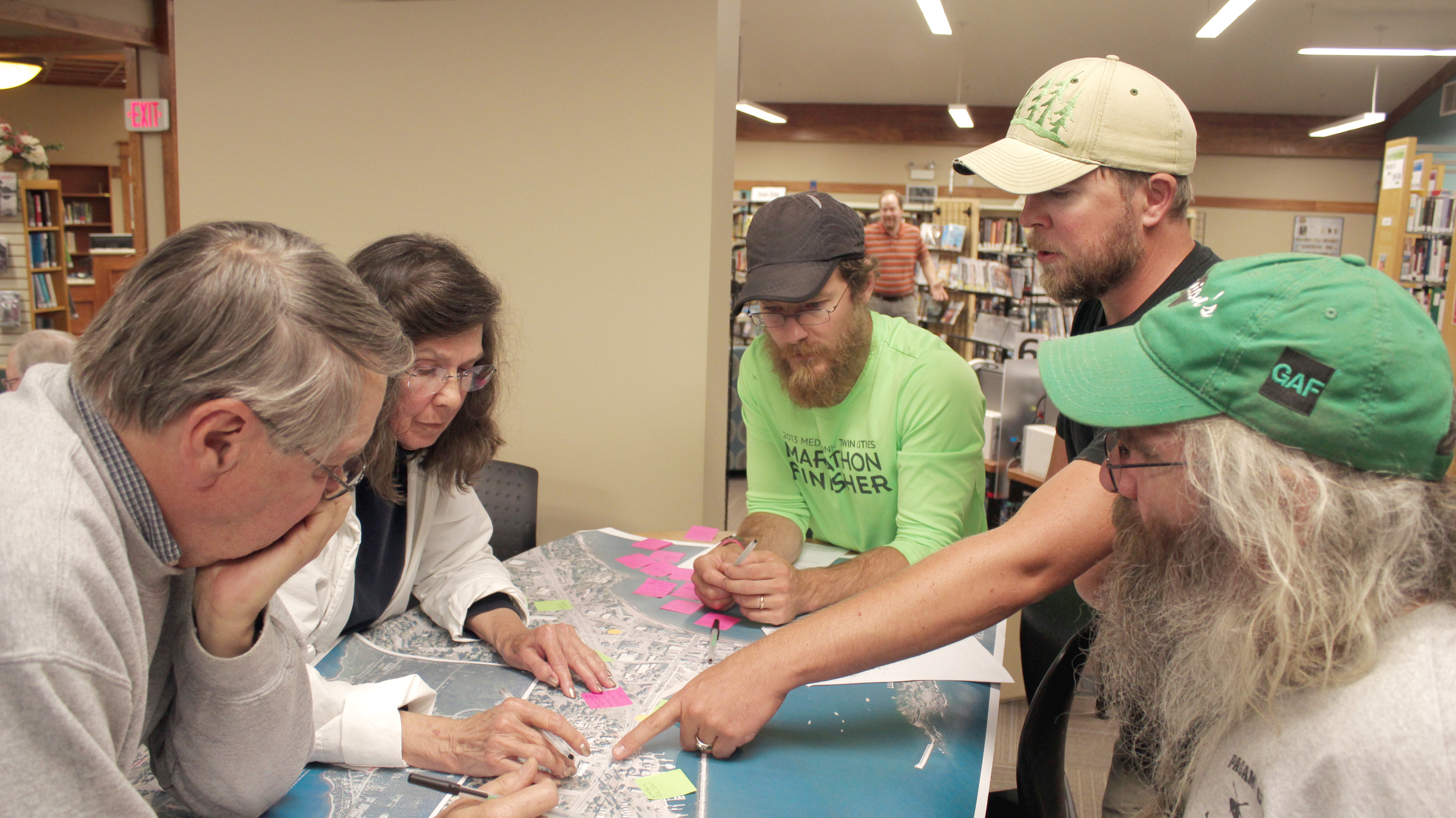A group of people engaged in a discussion around a table with a map on it