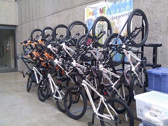 Several bikes in a vertical bike rack outside a school
