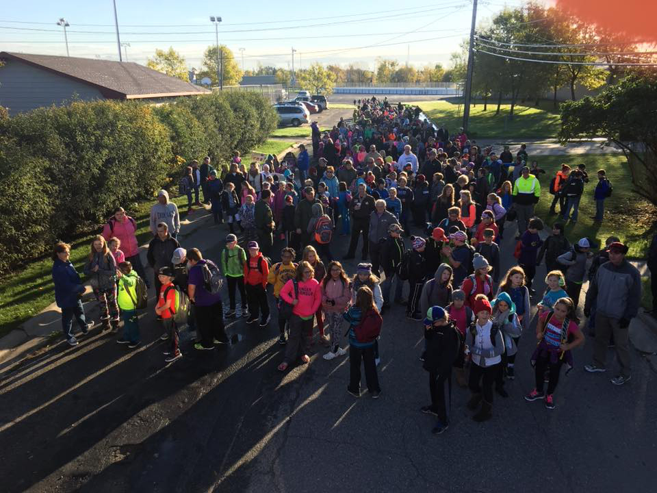 dozens of students standing in the school driveway