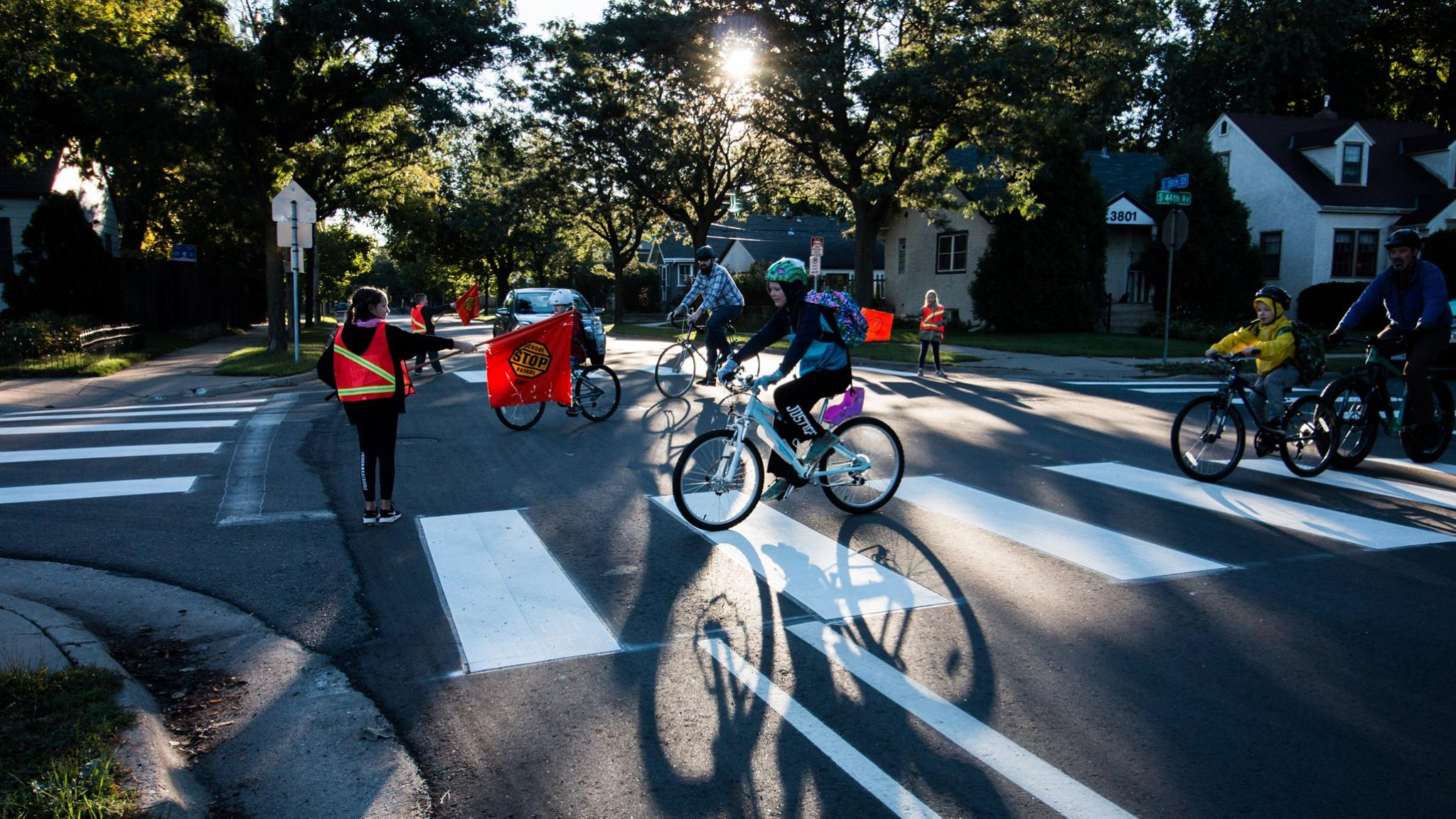 Photo of student safety patrol helping bicyclists cross the road