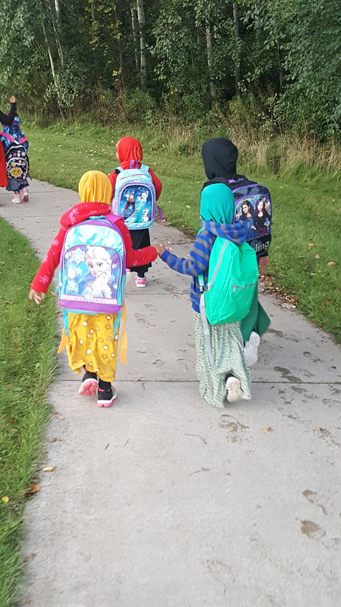 photo of two students walking while holding hands