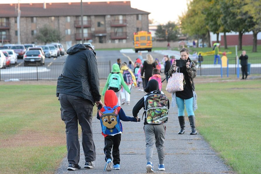 family holding hands while walking to school
