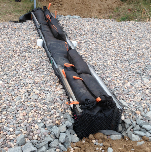 The iron-enhanced filter installed in this ditch check holds iron filings and sand in a geotextile fabric envelope and is supported by a metal filter cage extending across the swale. Topsoil and sod will cover the entire ditch check.