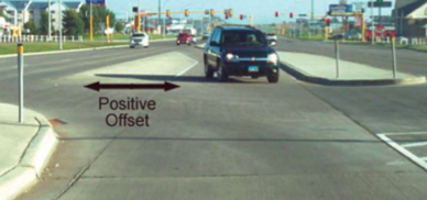 A vehicle waits in a left turning lane, separated by the main traffic lane by a concrete apron.