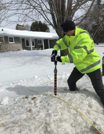 A researcher pushes a coring device into a snowbank along a city street.