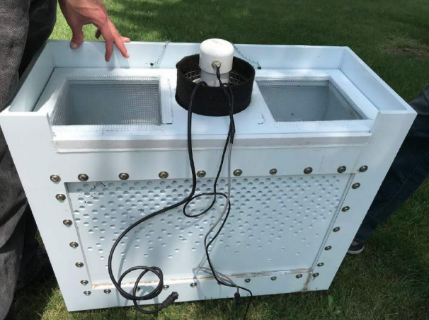 A rectangular white plastic box designed to collect street meltwater data. The box has perforated sides and a screened top. A cylindrical black-and-white instrument is mounted on the top with wire leads to transmit data.