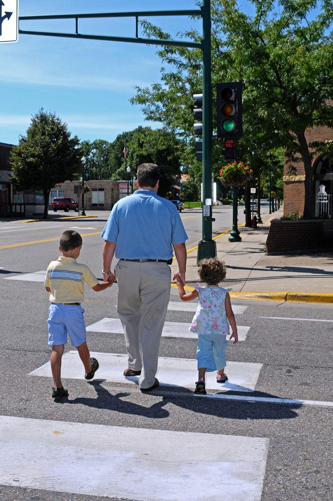 Family of three walks across pedestrian sidewalk.