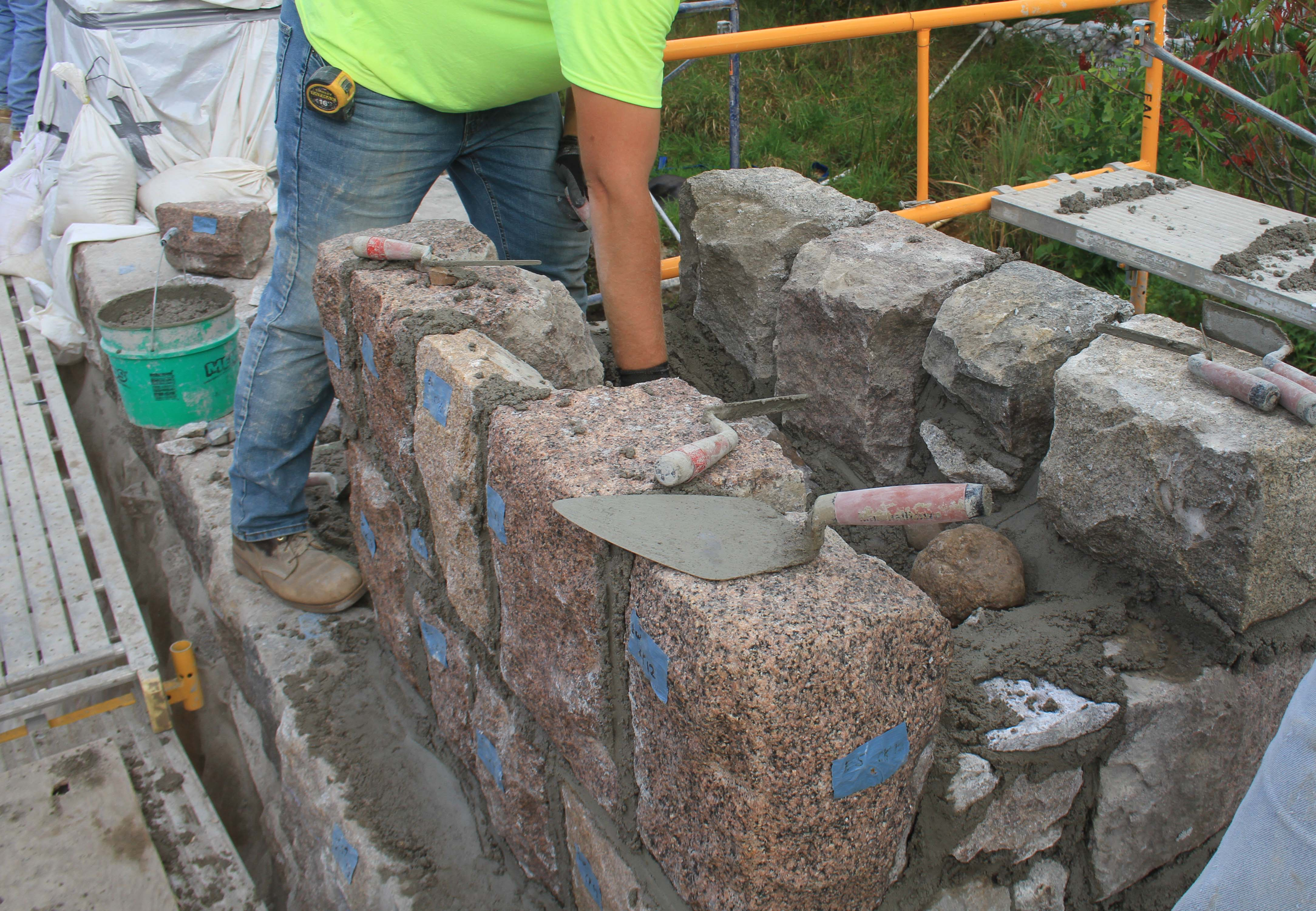 The stones are being carefully re-laid with new mortar in the same position they were in originally to reconstruct the bridge rail. September 2018.