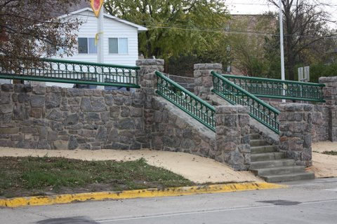 The same wall after restoration in 2011, featuring restored stone masonry and its steel rail back to the original color.