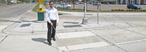 A vision-impaired citizen navigates a crosswalk.