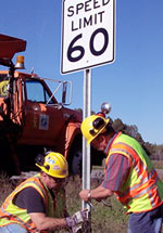 two construction workers putting in a speed limit 60 sign