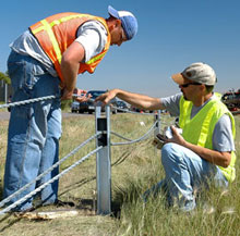Workers installing a cable median barrier.