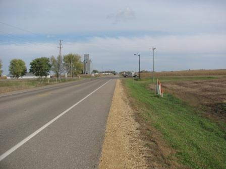 Rural two lane paved road with a sign showing a county highway.