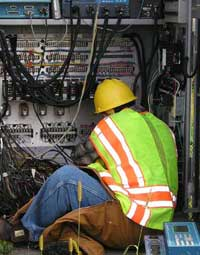 Electrician installing cables in the traffic signal cabinet