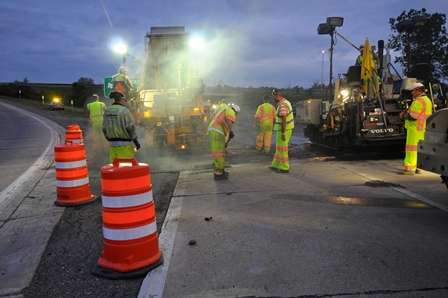 workers paving roadway at night