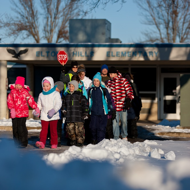 Students at Elton Hills elementary walking in front of school on a snowy day