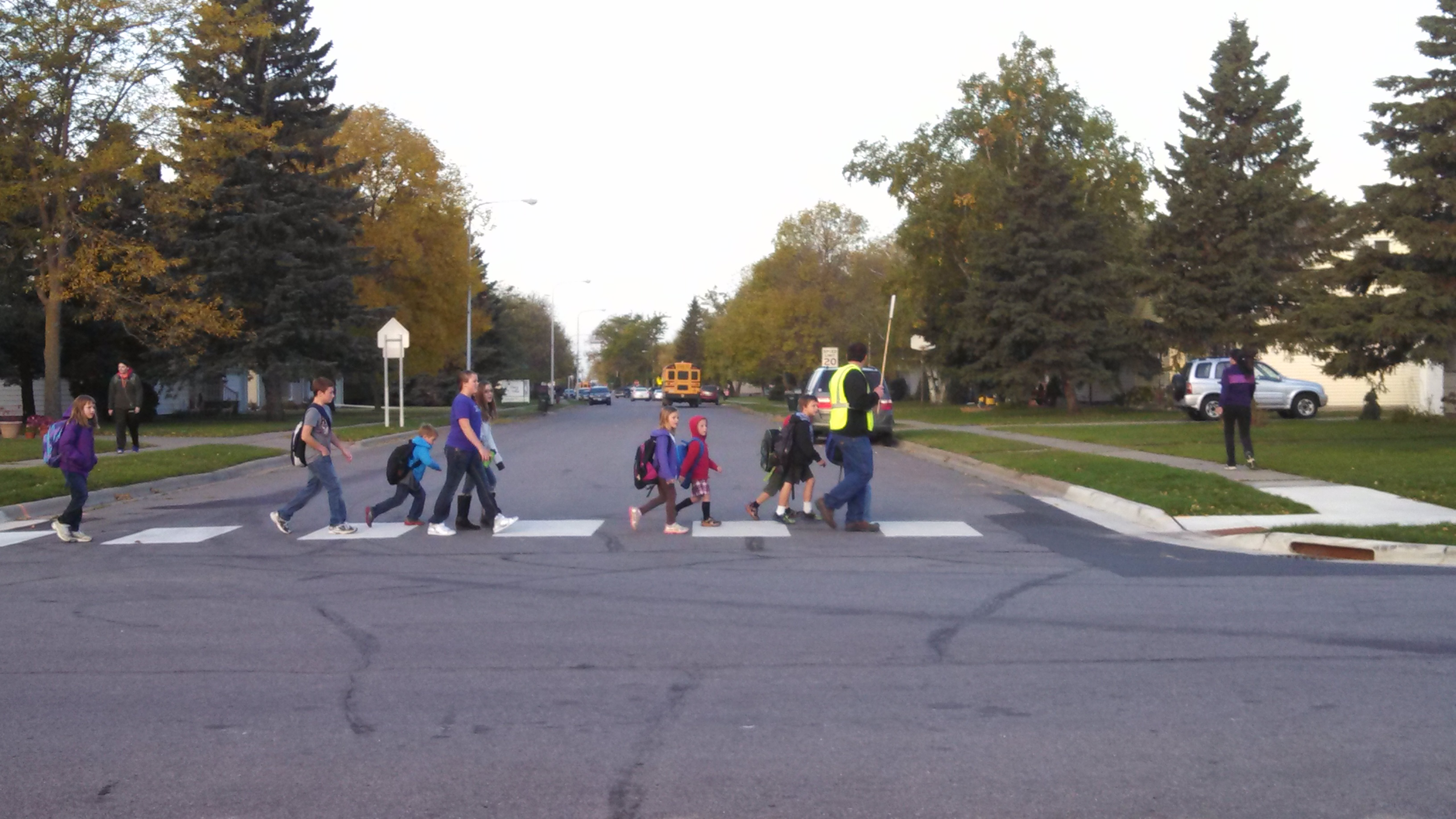 Crossing guard helping children across a street