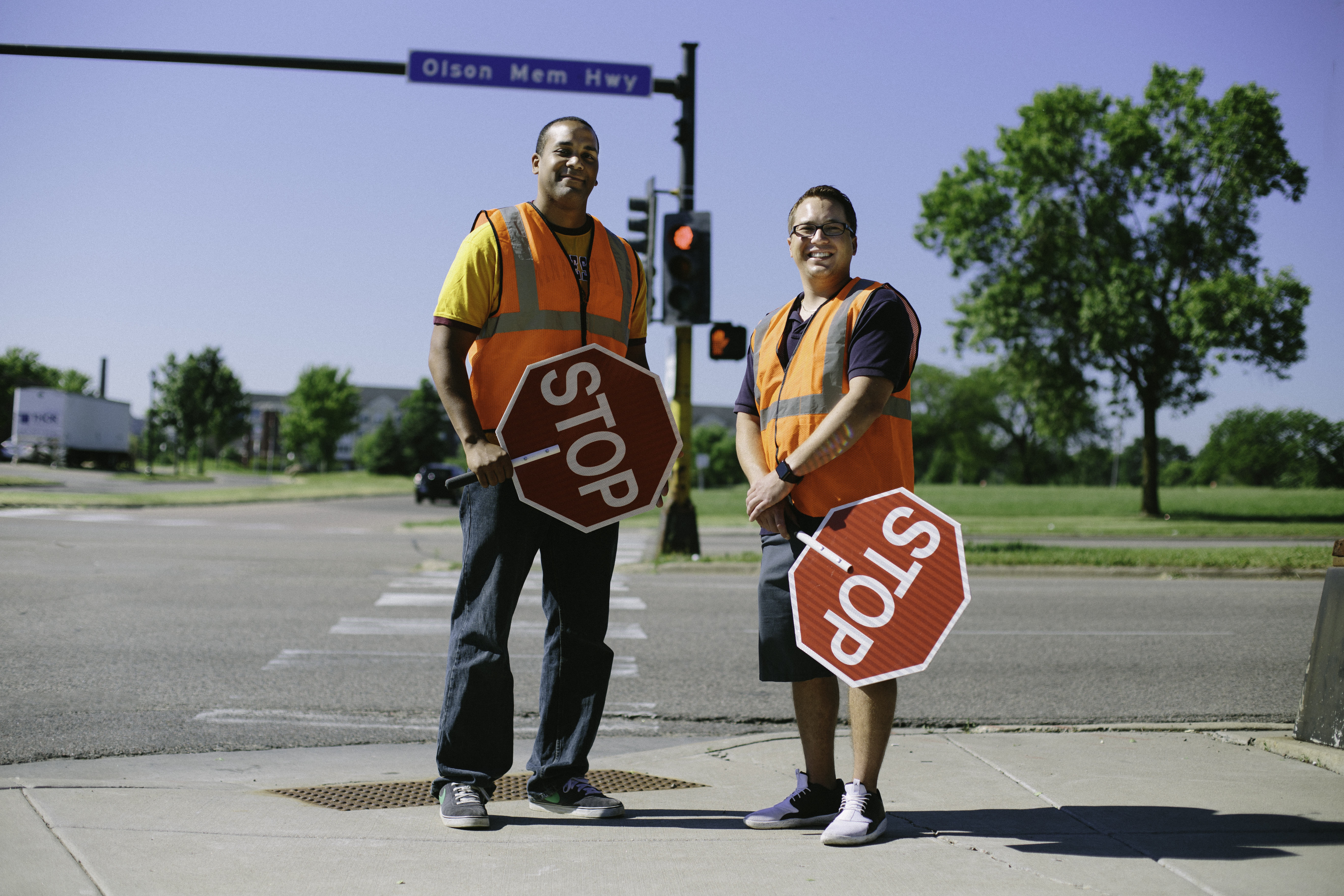 Two adults wearing reflective vests stand near a crosswalk and hold handheld stop signs