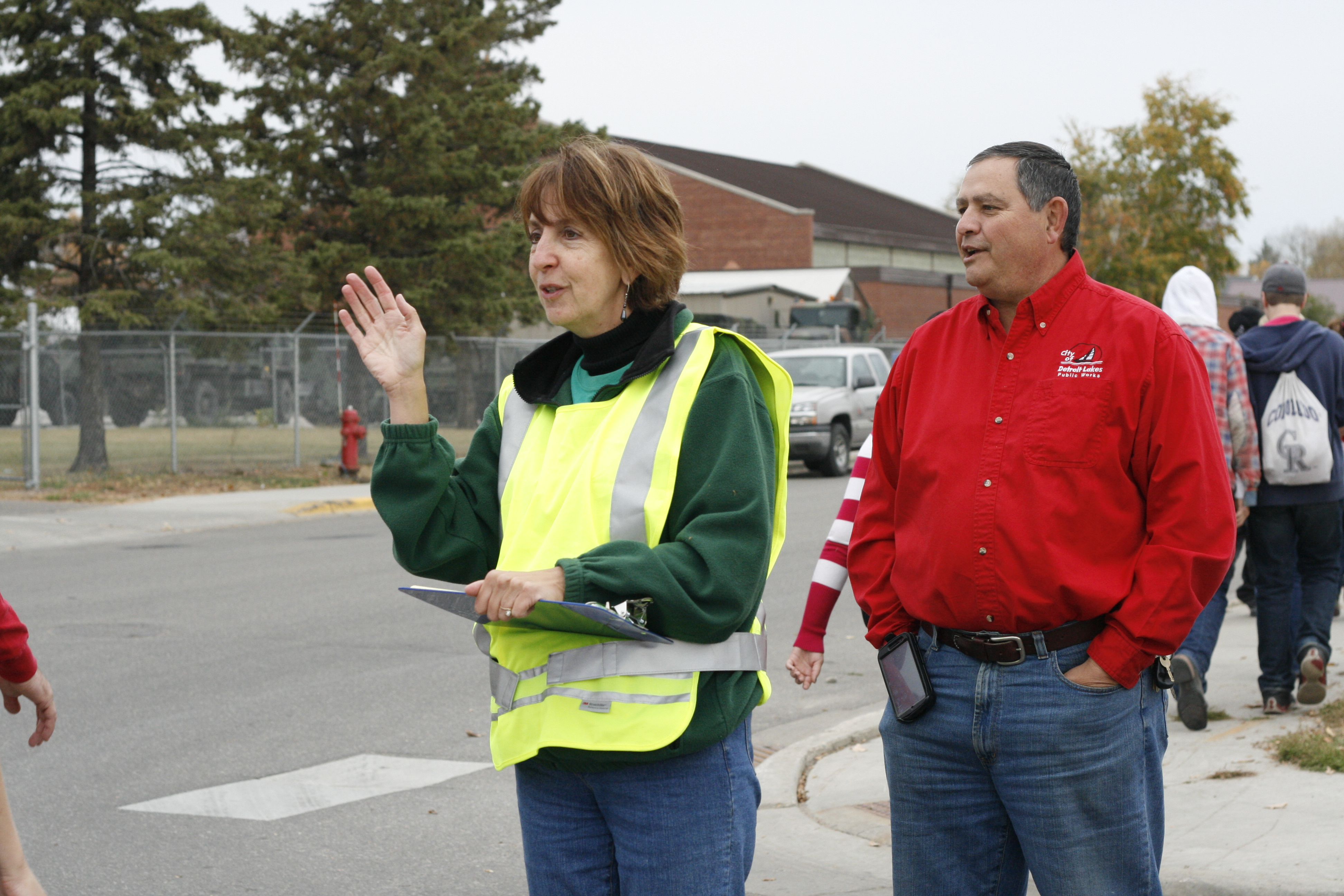 Two adults stand near a crosswalk, greeting students. One is wearing a reflective vest and holding a clipboard.