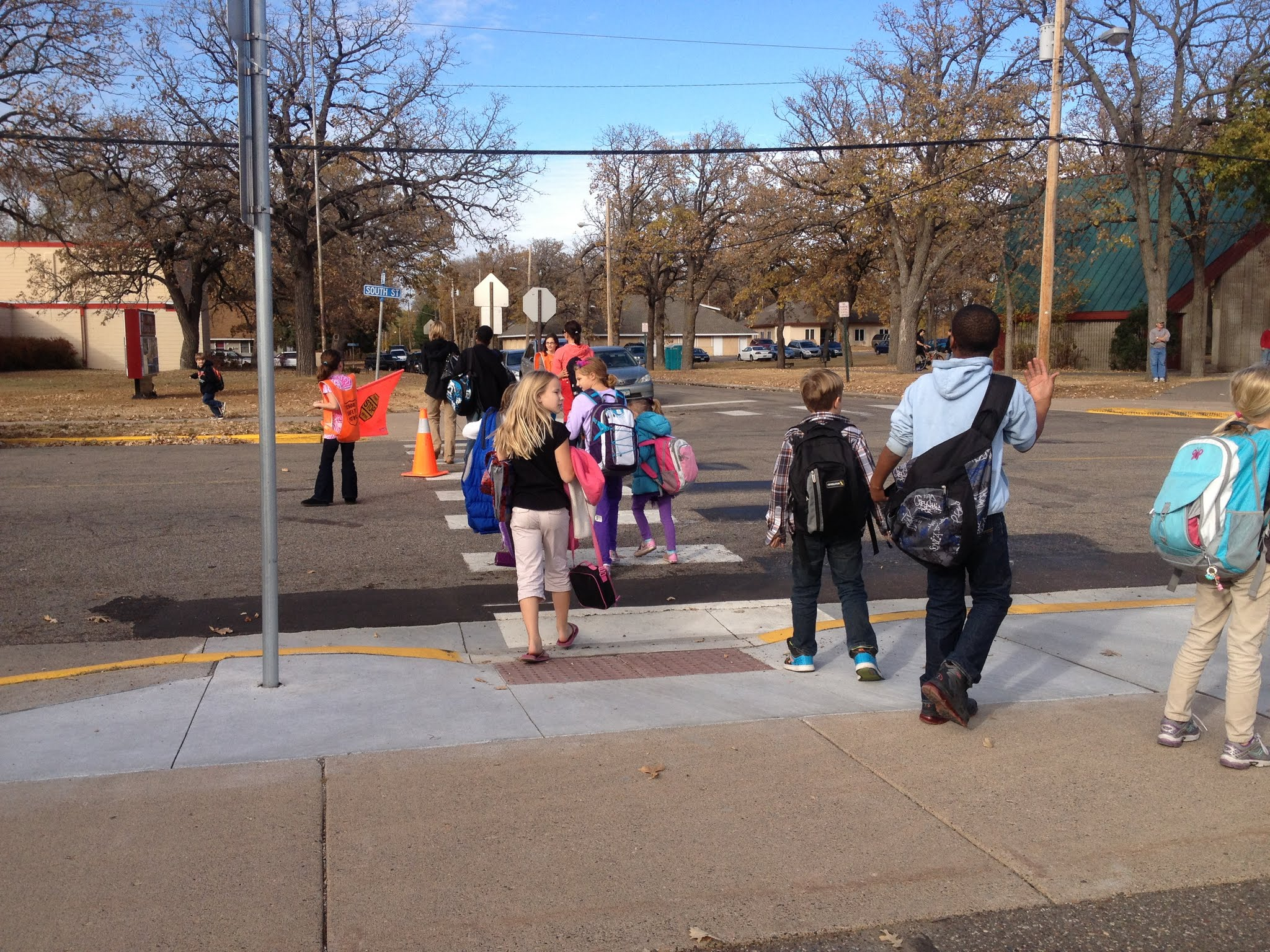 Children crossing a street in a crosswalk with help from a crossing guard
