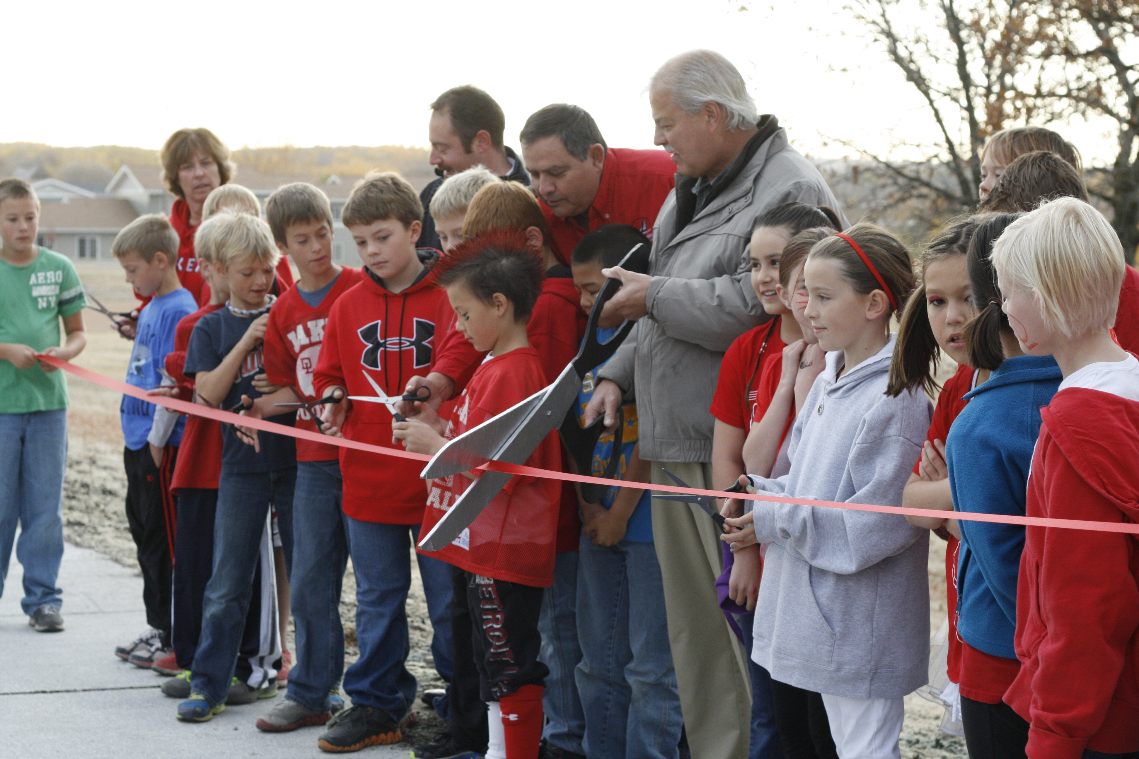 A group of children with an adult at a ribbon-cutting ceremony