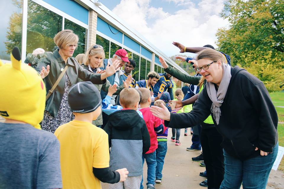 Teachers and football players give high-fives as students arrive at school