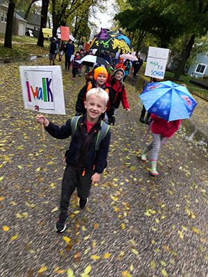 A group of children walk through puddles, some holding hand-written Walk to School Day signs and some holding umbrellas