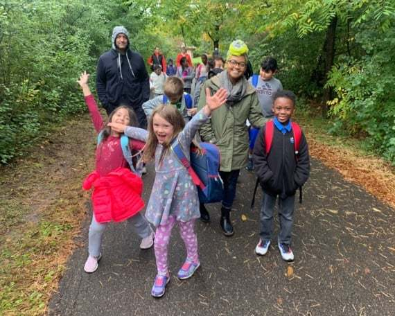 Students walk on a wooded trail with several adults. Two students are stiking a pose with their arms outstretched and big smiles.