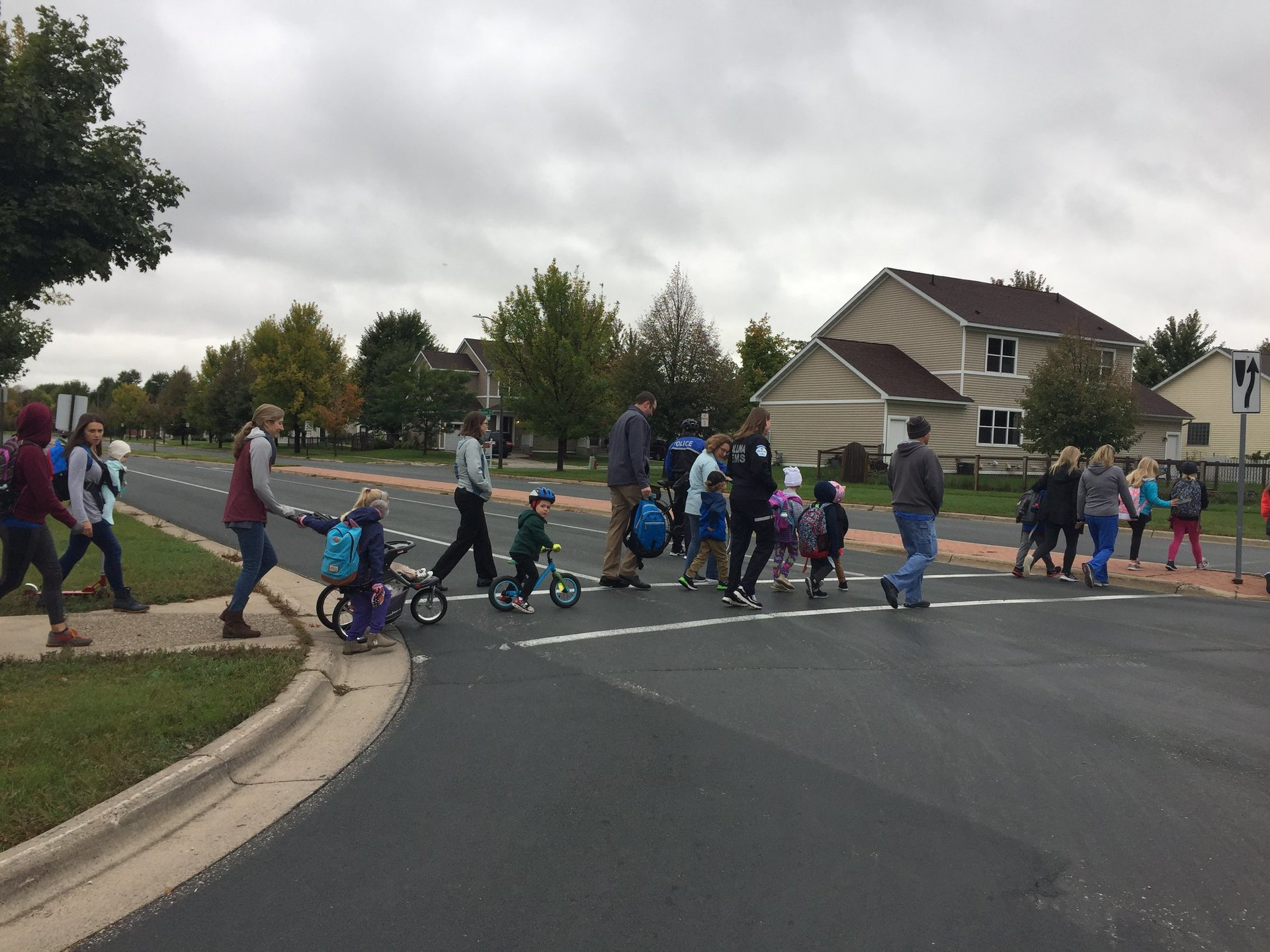 A group of students, and adults crosses the street in a crosswalk. Sone have bikes or strollers.