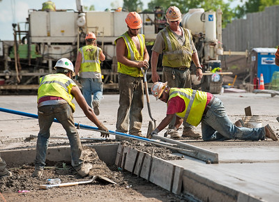 Workers in yellow vests construct a roadway.