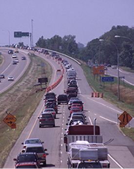Drivers using both lanes as they zipper merge into a single lane
